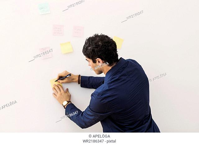 Rear view of young businessman writing reminders on adhesive note stuck on whiteboard