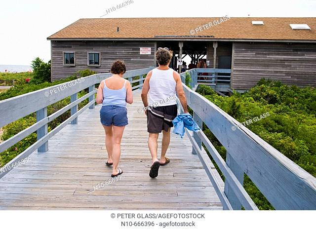 Couple walking up a wood ramp to the changing rooms at the beach
