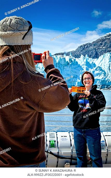 A young woman is taking a picture of her friend in front of Margerie Glacier on a tour boat, Tarr Inlet, Glacier Bay National Park & Preserve, Southeast Alaska