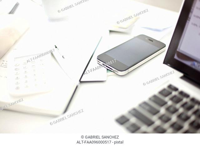 Smartphone resting on desk in in home office