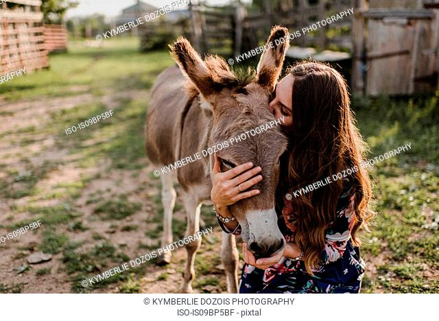 Woman kissing donkey