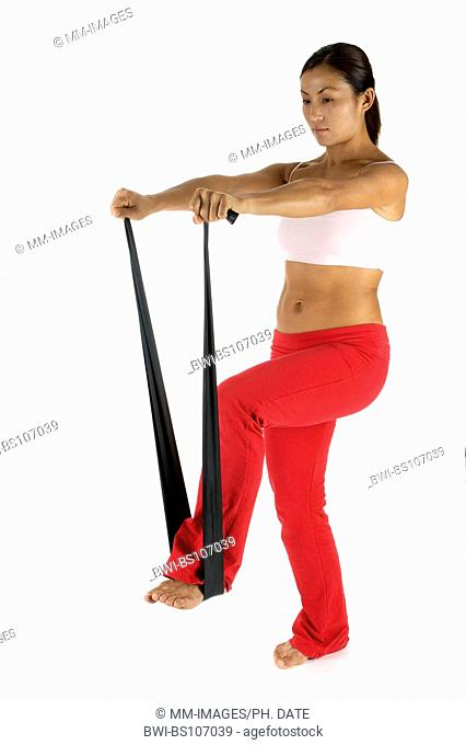 A female fitness instructor demonstrates an exercise using a training band