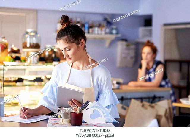 Woman working in a cafe taking notes
