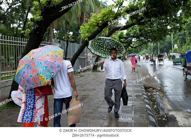 DHAKA, BANGLADESH - JUNE 07 : Peope walking on footpath during rain in Dhaka, Bangladesh on June 07, 2016