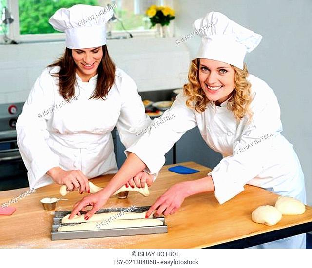 Female chef arranging prepared dough
