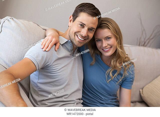 Portrait of a loving couple sitting on sofa