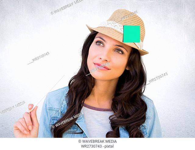 Thoughtful female executive wearing hat with sticky note against white background