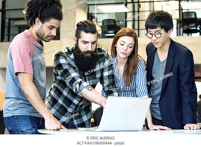 Colleagues working together with laptop computer