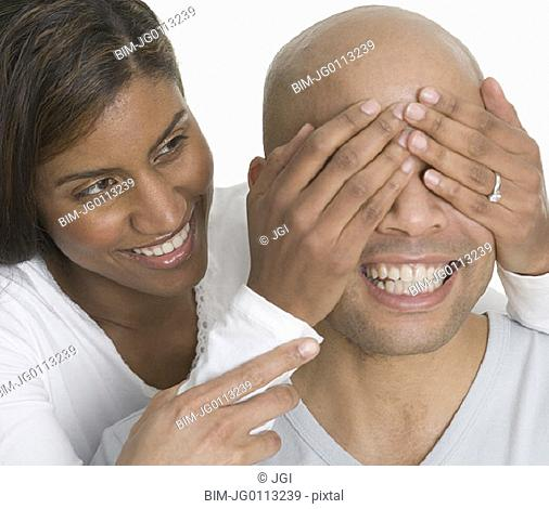 Woman with hands over man's eyes