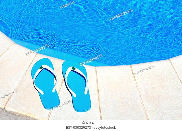 pair of blue flip-flops on the swimming pool