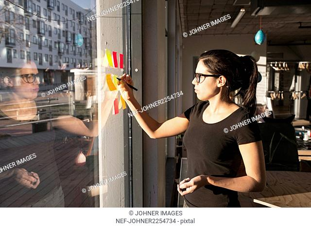 Woman sticking notes on window