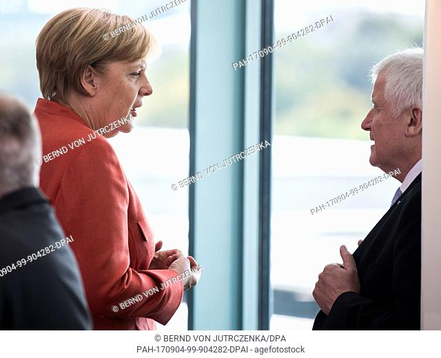German Chancellor Angela Merkel (l) and Horst Seehofer, Prime Minister of Bavaria (CSU), speak before the start of a meeting with the representatives of the...