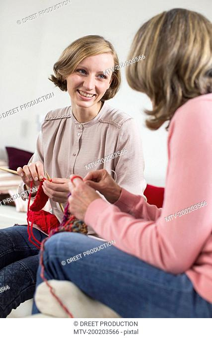 Mother and adult daughter knitting together