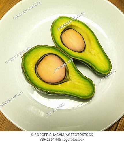 Ripe avocado pear cut in half, through the pip. On a white plate