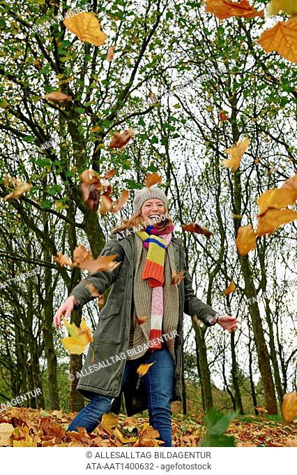 Woman throwing autumn foliage