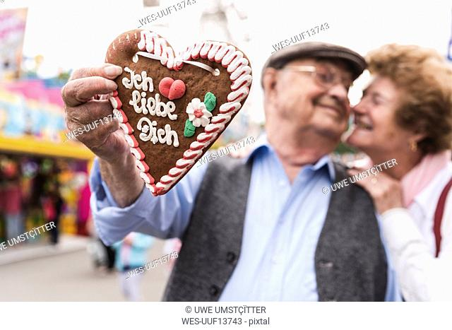 Hand of senior man holding ingerbread heart on fair, close-up