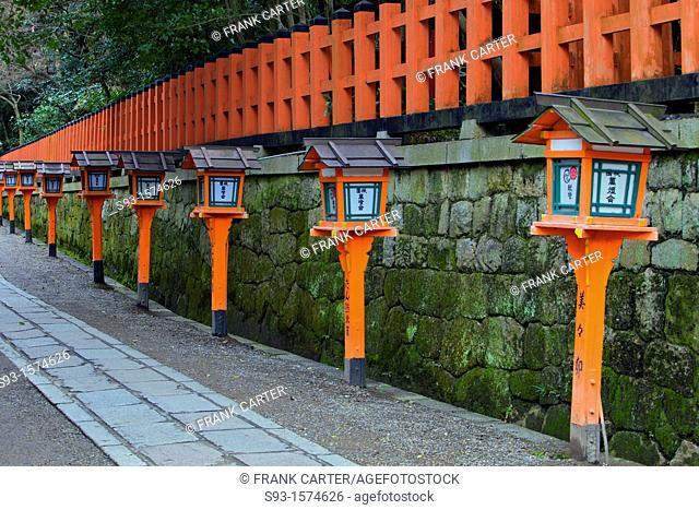 An orange fence and temple lights behind Yasaka Shrine