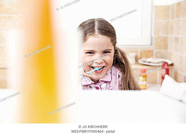 Germany, North Rhine Westphalia, Cologne, Portrait of girl brushing teeth in bathroom