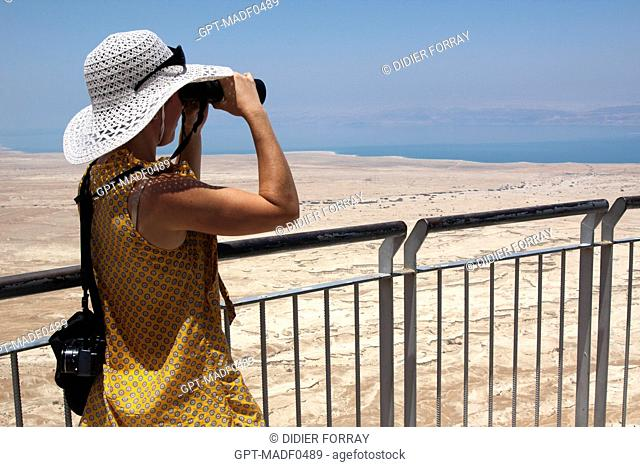 TOURIST LOOKING AT THE DEAD SEA THROUGH BINOCULARS FROM HEROD'S PALACE, SITE OF MASADA OR METZUDA, LISTED AS A WORLD HERITAGE SITE BY UNESCO, ISRAEL