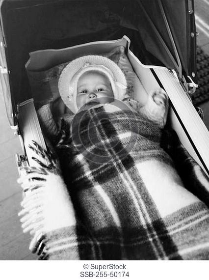 High angle view of a baby girl lying in a baby carriage