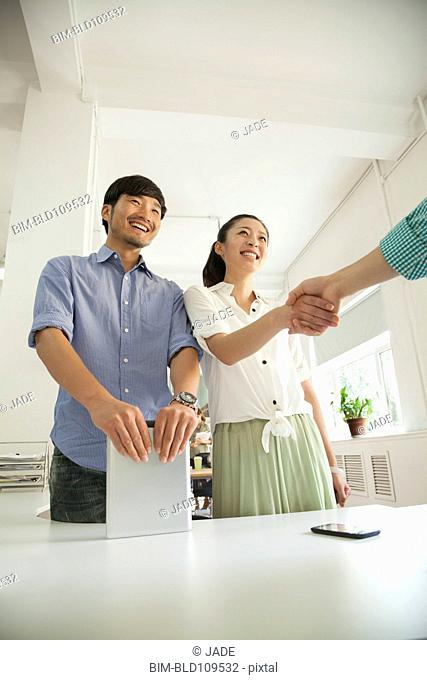 Chinese business people shaking hands at desk