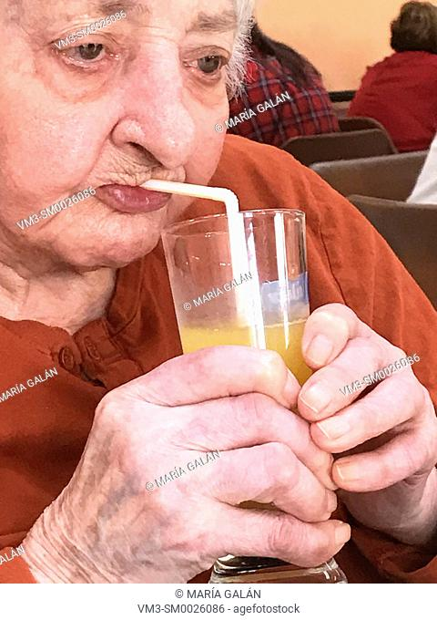 Old lady drinking a juice, using straw