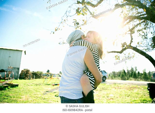 Mid adult woman and daughter hugging in sunlit park