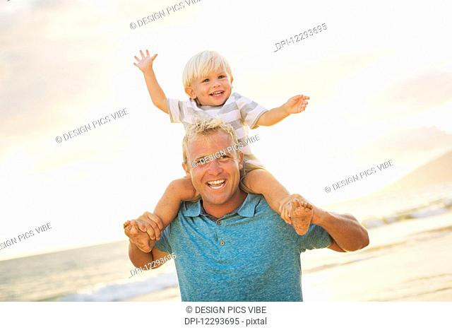 Father holding son on his shoulders on the beach at sunset