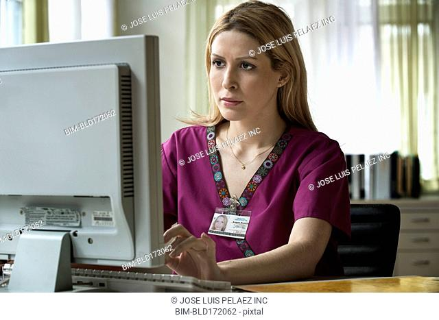 Mixed race nurse using computer in office