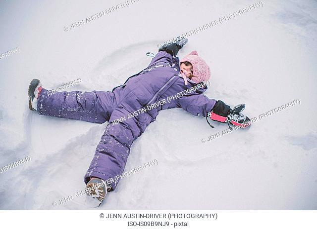 Young girl making snow angel in snow
