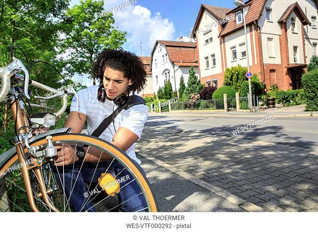 Young male student with racing cycle