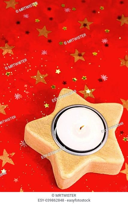 Burning candle and Chritmas decoration on red background