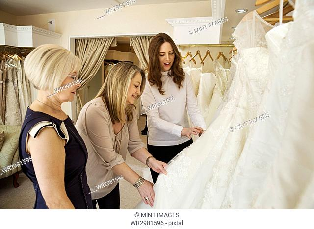 Three women, a client and two retail advisors in a wedding dress shop, looking through the choice of gowns