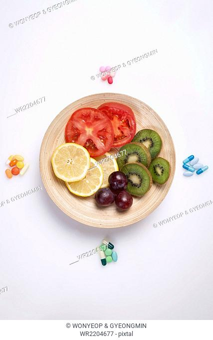 High angle of colorful vitamin pills around a plate with different color of vegetable slices and fruit slices