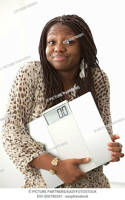 Teenage girl with a funny expression carrying a scale on white background