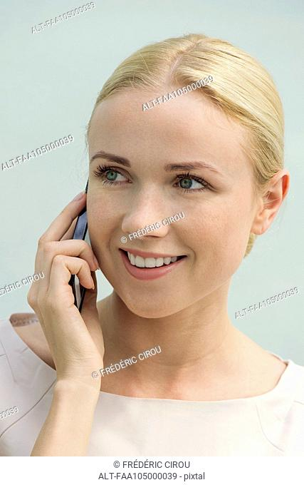 Woman talkiing on cell phone, smiling