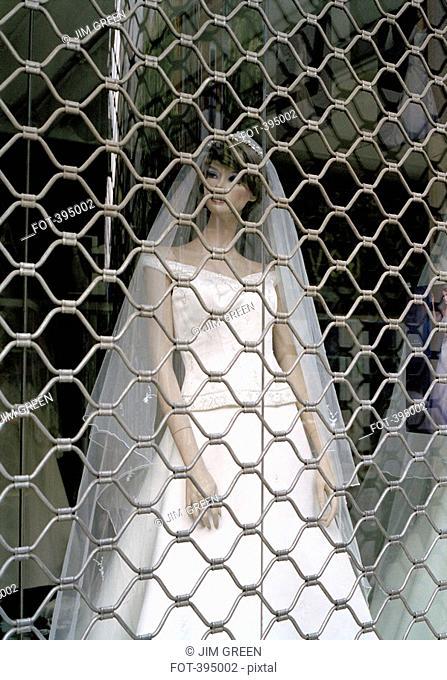 View of mannequin wearing wedding dress, through shop window