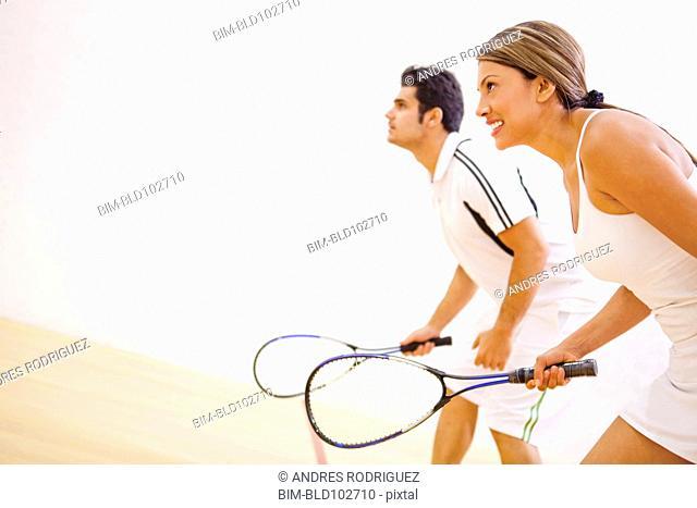 Hispanic couple playing squash