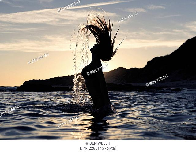 Silhouette of a woman in waist-deep water flipping her wet long hair up in the air; Tarifa, Cadiz, Andalusia, Spain