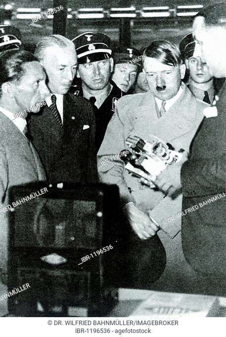 Josef Goebbels and Julius Schaub explain the Volksempfaenger radio to Adolf Hitler, historical photo circa 1936