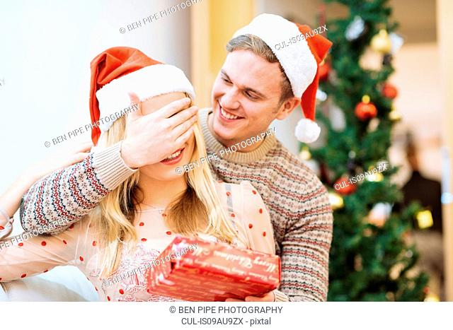 Young man covering girlfriends eyes whilst handing christmas present