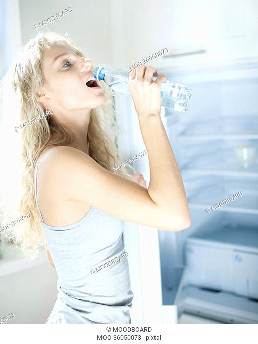 Side view of young woman drinking water from bottle by refrigerator