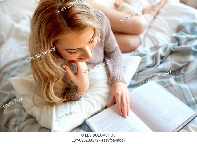 rest, comfort, leisure and people concept - close up of happy young woman reading book in bed at home bedroom