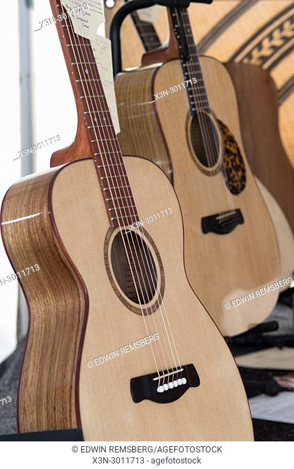 Two hand-made guitars resting on stands for sale