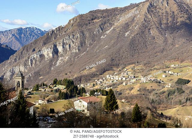 landscape with mountain village near the rocky slope of Menna peak in Bergamo mountains in a winter with little snow , shot in bright winter light