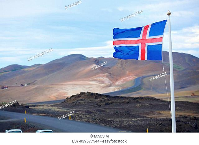 The flag of Iceland waving in the wind?on a background of a stormy sky