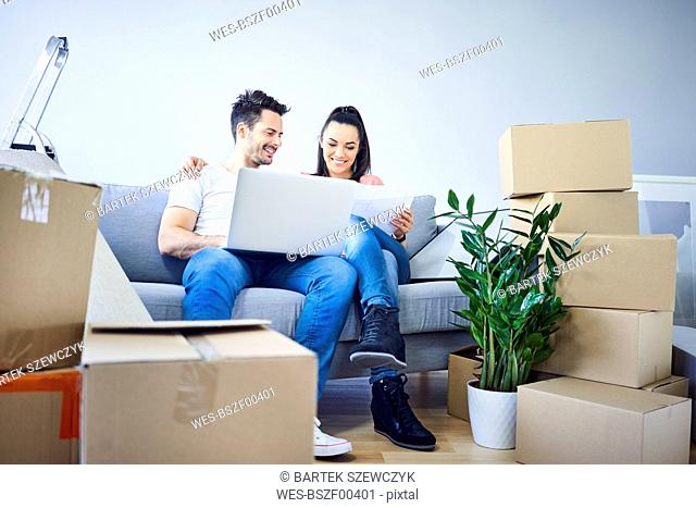 Happy couple sitting on couch surrounded by cardboard boxes using laptop