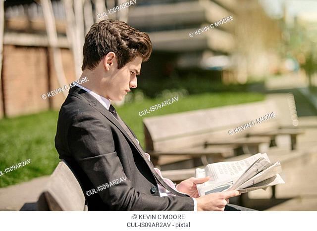 Young city businessman sitting on bench reading newspaper