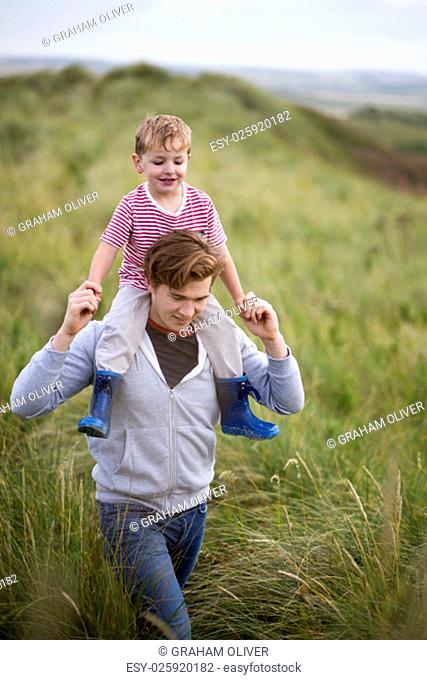 Portrait of a father and son walking through long grass next to a beach. The little boy is on his fathers shoulders and they are both smiling