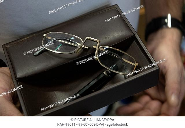 17 January 2019, Berlin: The reading glasses and a pen by Winnetou actor Pierre Brice are held by a man in an auction house